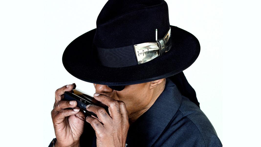 Stevie Wonder trägt Hut und spielt Mundharmonika.